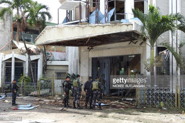 Policemen and soldiers stand outside bombhit church in Jolo Sulu province on the southern island of Mindanao on January 27 2019 At least 18 people...