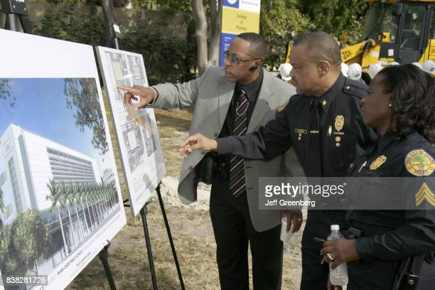 Policemen and woman looking at architectural rendering plans at the groundbreaking ceremony for the College of Policing