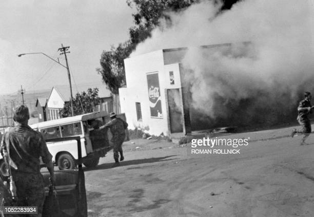 Policemen are about to fire on demonstrators after a shop has been looted and burned during a protest against having to use Afrikaans language at...
