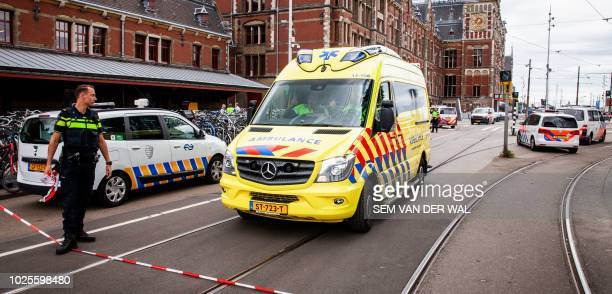 Policemen are at work after a stabbing incident at the central station in Amsterdam on August 31 2018 The Police have shot a suspect after two people...