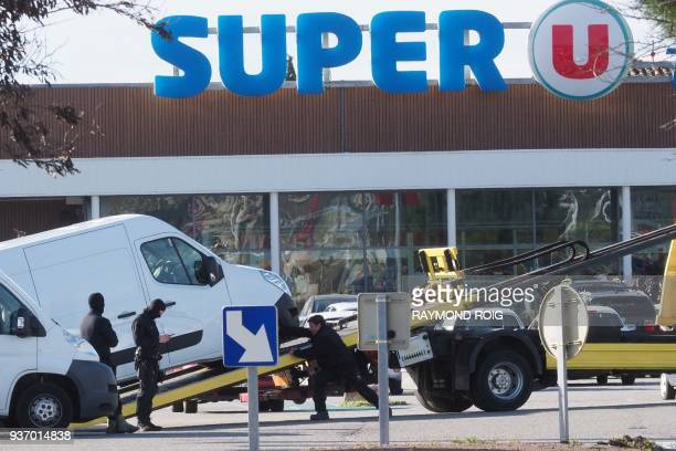 Policemen are at work as a van is taken away outside the Super U supermarket of Trebes southern France on March 23 after special forces killed a...