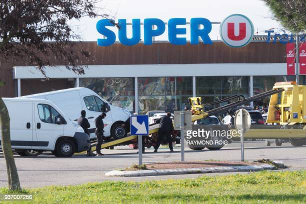 Policemen are at work outside a Super U supermarket in the town of Trebes southern France on March 23 after special forces killed a gunman who had...