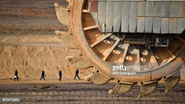 TOPSHOT Policemen are seen behind a bucketwheel excavator as they secure the area of the Hambach lignite open pit mine near Elsdorf western Germany...