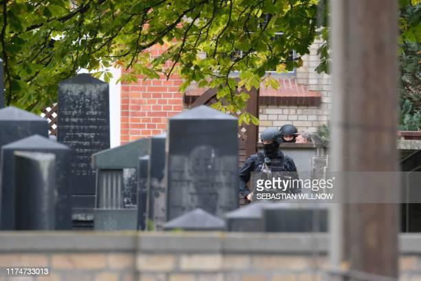 Policemen are seen behind gravestones of a Jewish cemetery close to the site of a shooting in Halle an der Saale eastern Germany on October 9 2019 At...