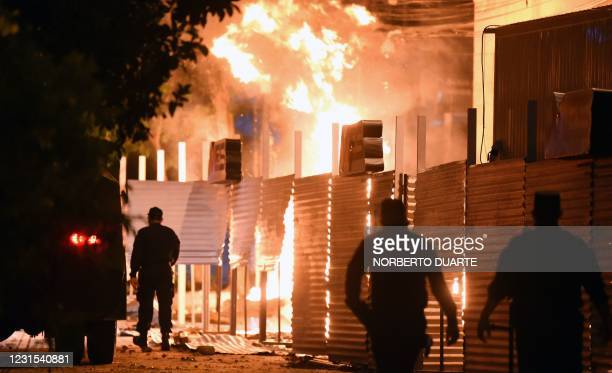 Policemen are seen near a fire set on by demonstrators at the Commerce Ministry headquarters during a protest against corruption and lacks in the...