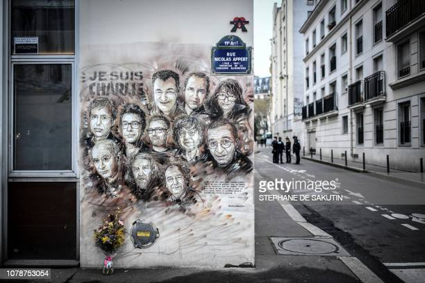 Policemen are seen next to a painting by French street artist and painter Christian Guemy, known as C215, in tribute to members of Charlie Hebdo...