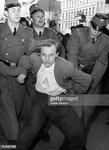 Policemen arrest a communist demonstrator outside the flat of Doctor Pawloff a French physician and communist who has been forced to stop his...