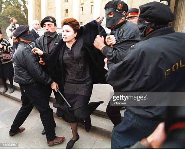 Policemen arrest a demonstrator who displayed a placard in front of the Parliament building to protest against the leader of the Georgian government...