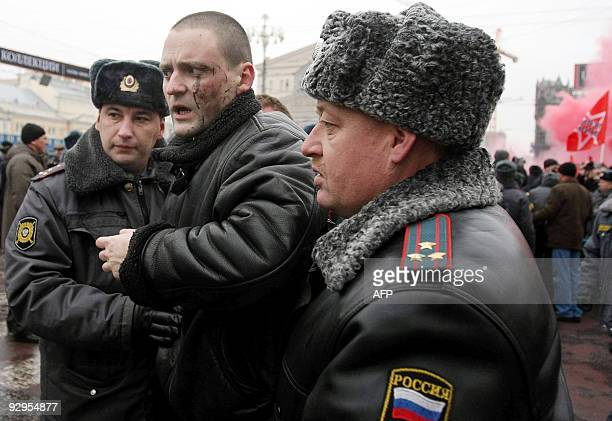 Policemen arrest a facebleeding supporter of the Russian Communist party during their march in Moscow on November 07 marking the 92th anniversary of...