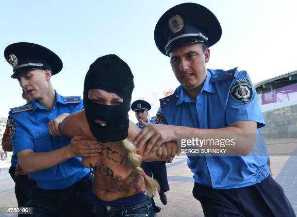 Policemen arrest activists of Ukrainian women's movement FEMEN protesting in front of the Olympic stadium in Kiev against the UEFA and against the...