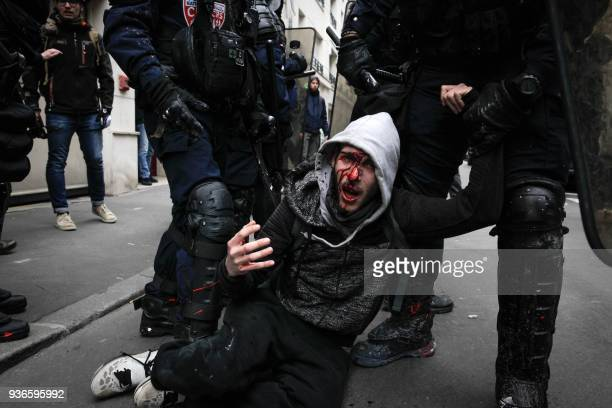 TOPSHOT Policemen arrest an injured man on the sidelines of a protest against French government's string of reforms on March 22 2018 in Paris Seven...