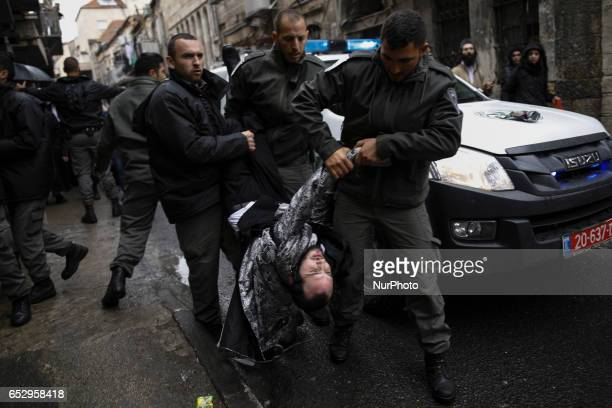 Policemen arrest an ultraOrthodox man during clashes after a soldier doll was hung from a building as part of the ultraOrthodox Jewish protest...
