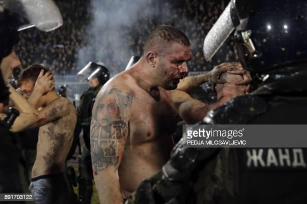 TOPSHOT Policemen arrest Partizan Belgrade's hooligans after clashes between two groups of Partizan Belgrade's supporters during the Serbian...