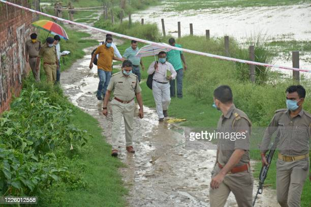 Policemen arrive at the scene to investigate after the gangster Vikas Dubey was shot dead by police, on a highway at Sachendi in Uttar Pradesh state...