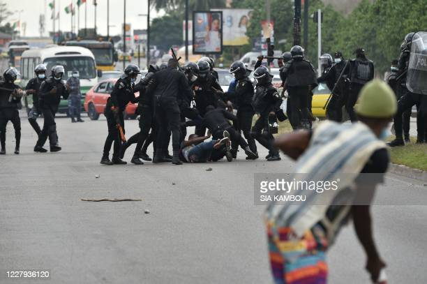 TOPSHOT Policemen beat a demonstrator during a rally of former Ivory Coast President Laurent Gbagbo's supporters to protest against his absence on...