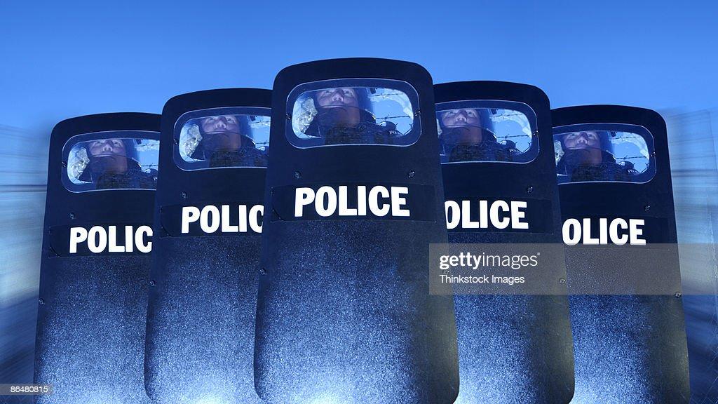 Policemen behind shields : Stock Photo