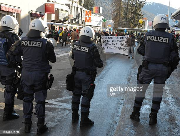 Policemen block protesters demonstrating against the World Economic Forum on January 26 2013 in a street of Davos The meeting gathers some of the...