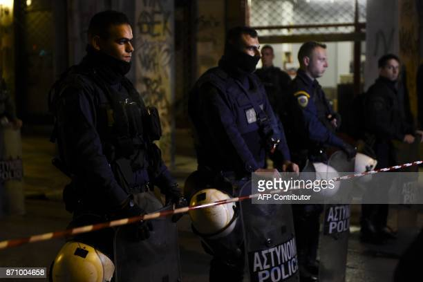 Policemen block the street after a gunman fired riot police guarding the headquarters of the Greek Socialist Party Pasok in Athens on November 6...