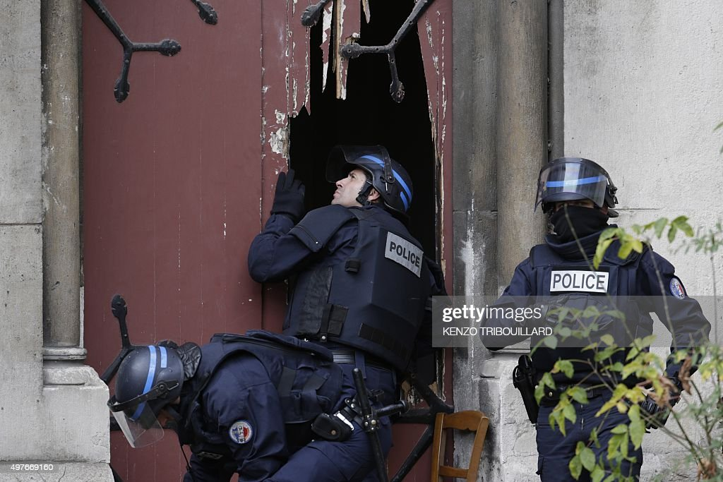 Policemen break a door to enter a church in the northern Paris suburb of Saint-Denis city center, on November 18, 2015, to secure the area after French Police special forces raid an appartment, hunting those behind the attacks that claimed 129 lives in the French capital five days ago. At least one person was killed in an apartment targeted in the operation aimed at the suspected mastermind of the attacks, Belgian Abdelhamid Abaaoud, and police had been wounded in the shootout.