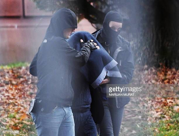 Policemen bring a suspect person to the Federal German Prosecutor on November 8 2016 in Karlsruhe southern Germany after German police arrested five...