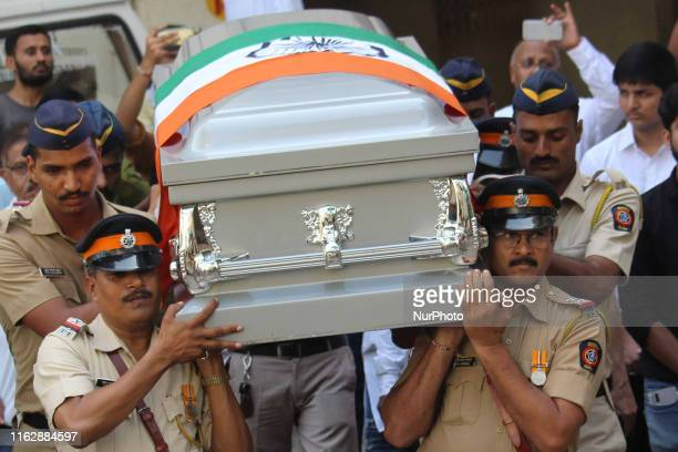 Policemen carry a coffin containing the body of veteran Indian music composer Mohammed Zahur Khayyam Hashmi as they pay tribute during his funeral...