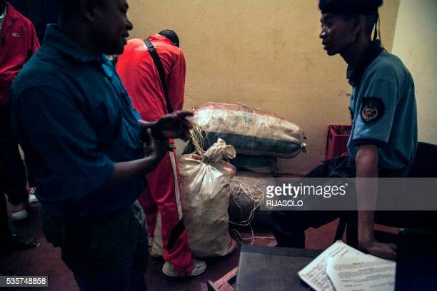 Policemen carry bags of vanilla as about 260 kg of green vanilla have been seized by gendarmerie and representative of Government and stored at the...