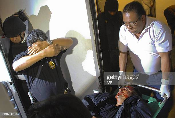 Policemen carry the corpse of a partner dead after an assault on a police station in Oxaca on December 1 2008 Three of nine beheaded men who appeared...
