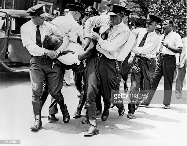 Policemen carrying a World War I veteran a member of the Bonus Expeditionary Forces from a building on Pennsylvania Avenue during the riots that were...