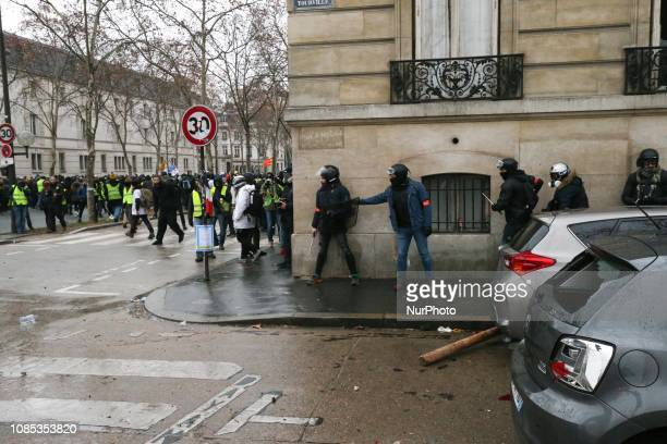 Policemen charge Gilets Jaunes demonstrators at the corner of the street in front of the Hotel national voice over Invalides in Paris on January 19...