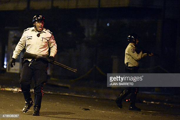 Policemen chase demonstrators during a protest against Venezuelan President Nicolas Maduro in Caracas on March 13 2014 Police in protesthit Venezuela...
