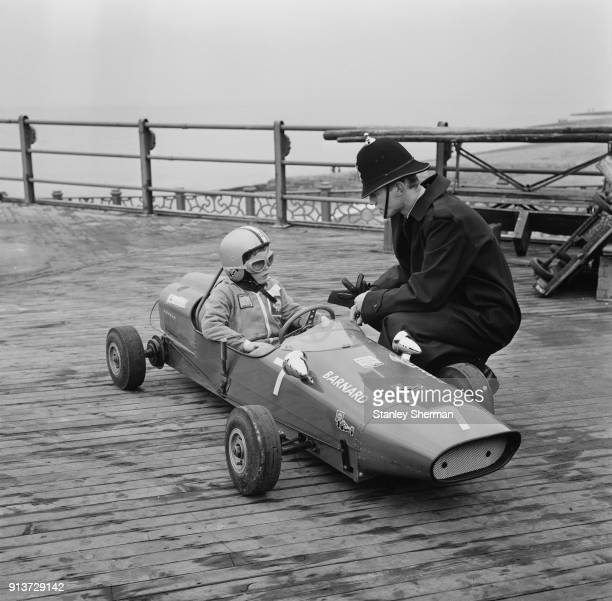 A policemen chats with a kid driving a miniature car at the Brighton Toy Fair UK 28th January 1968