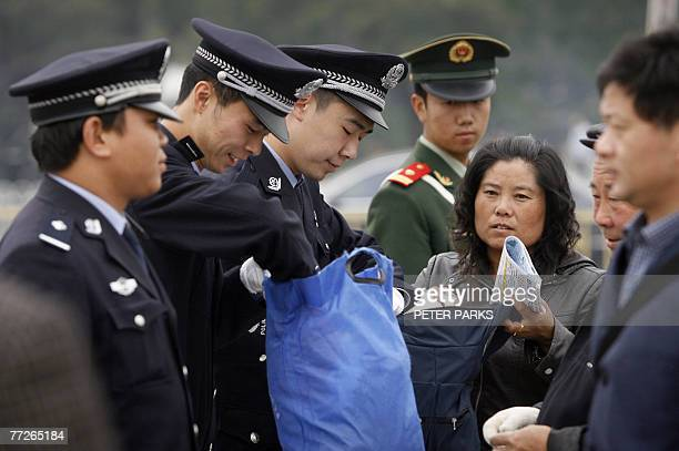 Policemen check bags on Tiananmen Square in Beijing, 11 October 2007, as China's ruling Communist Party has intensified a crackdown on dissent ahead...