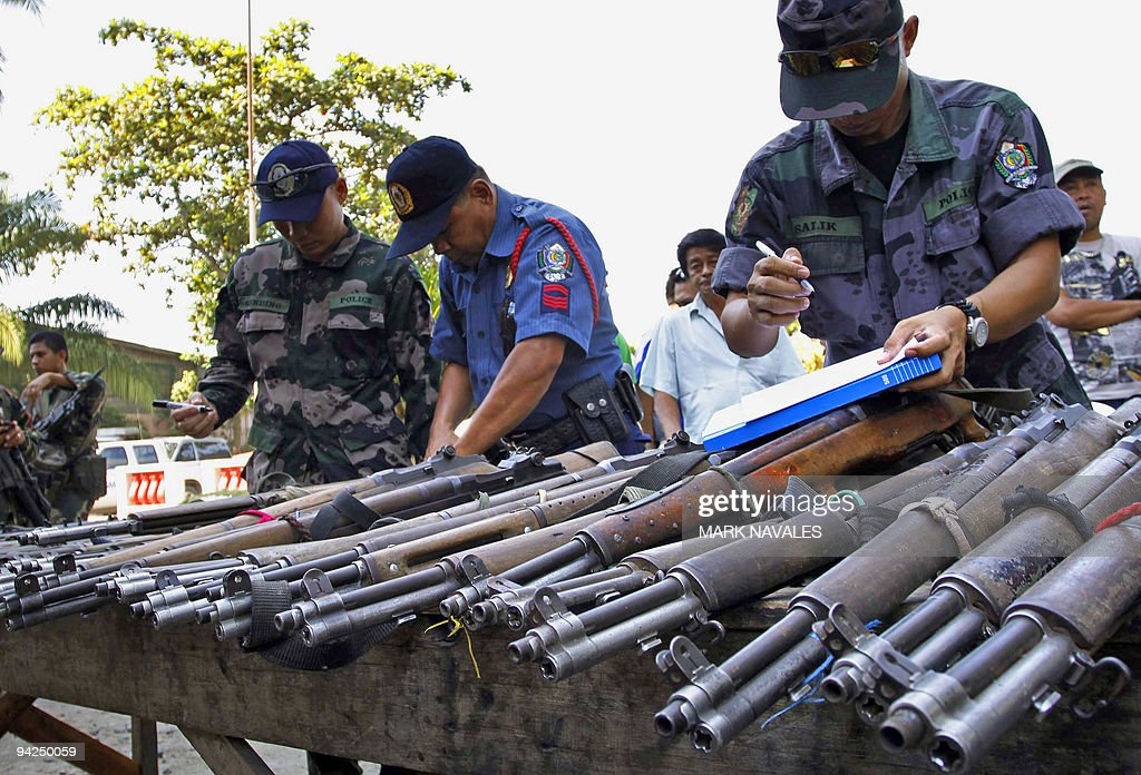 Policemen check firearms surrenderd by c : News Photo