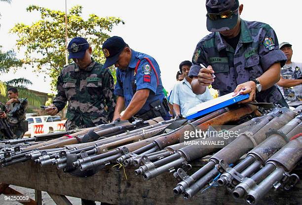 Policemen check firearms surrenderd by civilian volunteers not directly under the powerful Ampatuan clan in Datu Piang in Maguindanao province on...