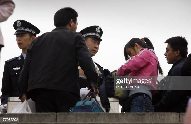 Policemen check pedestrians' bags at Tiananmen Square in Beijing, 11 October 2007, as China's ruling Communist Party has intensified a crackdown on...