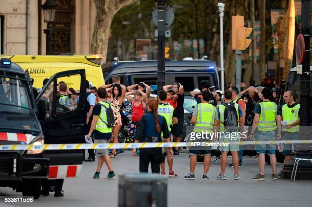 Policemen check the identity of people standing with their hands up after a van ploughed into the crowd killing two persons and injuring several...