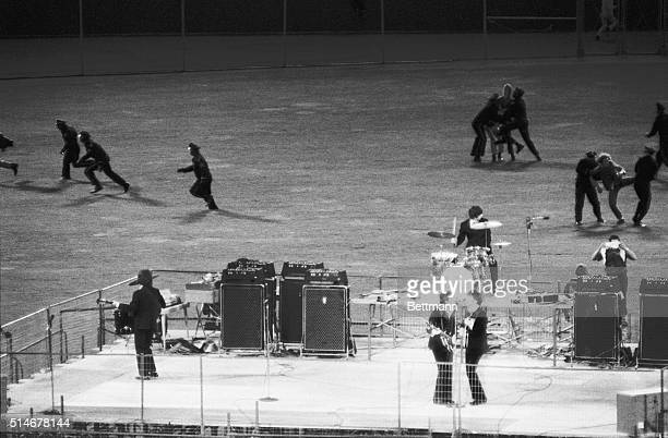 Policemen clear the field of enthusiastic fans as The Beatles perform on a bandstand in Candlestick Park San Francisco California