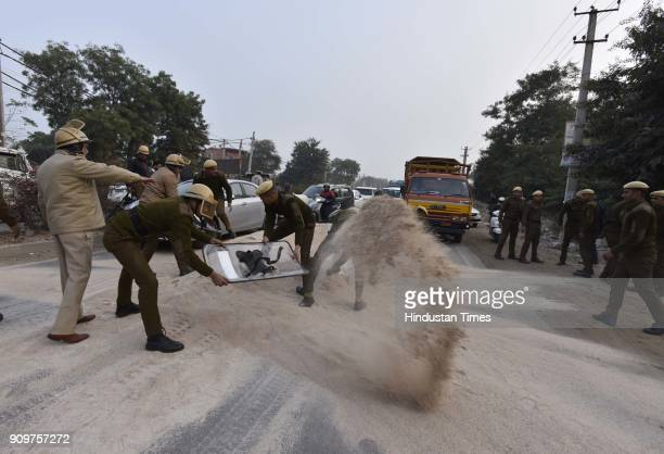 Policemen clearing out the pile of gravel dumped on road in order to block the traffic near village Bhondsi in Gurgaon allegedly by activists of...