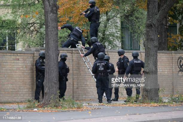 Policemen climb over a wall close to the site of a shooting in Halle an der Saale eastern Germany on October 9 2019 At least two people were killed...