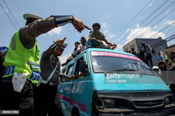 Policemen conduct a security to avoid protesters from attacking online taxis in Makassar South Sulawesi province on November 1 during a rejection of...