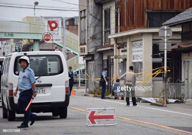 Policemen conduct investigations in front of a police station where a colleague was stabbed in central Toyama prefecture on June 26 2018 Two people...