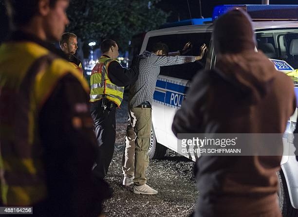 Policemen control a man from France suspected of trafficking people from Afghanistan to Europe at the GermanAustrian border near Piding southern...