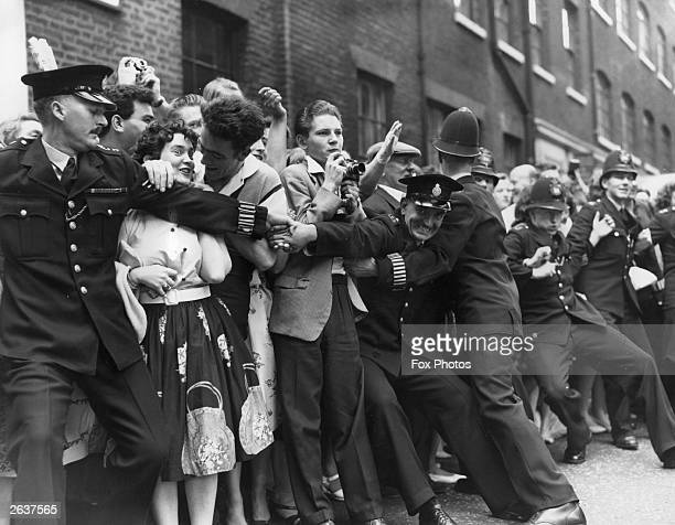 Policemen controlling fans of the rock and roll singer Tommy Steel outside Saint Patrick's Church Soho Square where he is to be married to Ann...