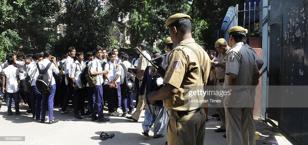Policemen controlling students of Government Boys Senior School at Chittaranjan Park after their protest against the Principal over injury of class 4th student Roshan Lama on October 3, 2013 in New Delhi, India. 11 year old boy Roshan Lama is battling for life at AIIMS Trauma Centre after a javelin, thrown by a senior student during a practice session, pierced his skull at a school playground in CR Park area of south Delhi two days ago.