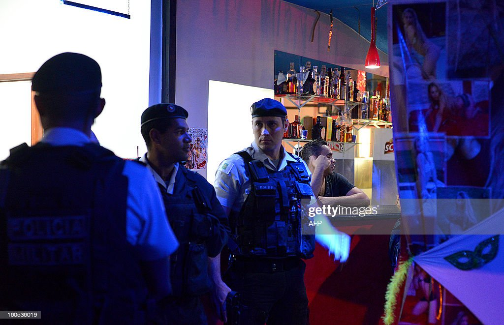 Policemen converse during the inspection of a nightclub in a suburb of Brasilia, on February 2, 2013. The Brazilian authorities ordered the inspection of many bars and nightclubs all over the country after the blaze in the Kiss Nightclub in Santa Maria, southern Brazil, that left more than 230 people dead. AFP PHOTO/ Pedro LADEIRA STR /pl/pa