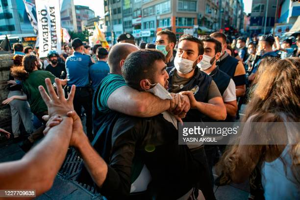 Policemen detain a man during a protest marking the anniversary of the 2015 suicide attack in the southern Turkish town of Suruc, in the Kadikoy...