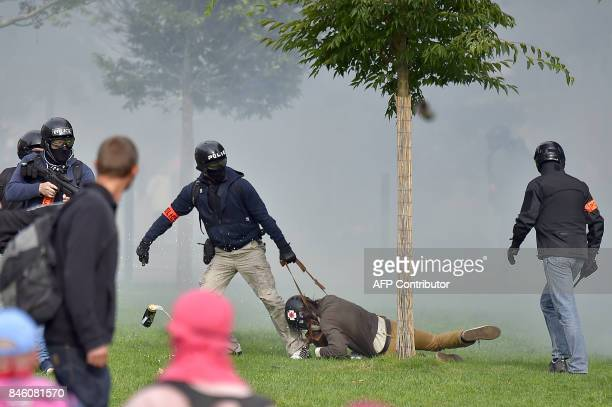 TOPSHOT Policemen detain a protester during clashes within a protest called by several French unions against the labour law reform on September 12...