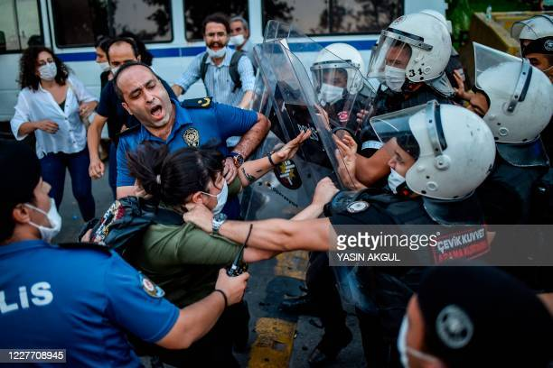 Policemen detain a woman during a protest to mark the anniversary of the 2015 suicide attack in the southern Turkish town of Suruc, in the Kadikoy...