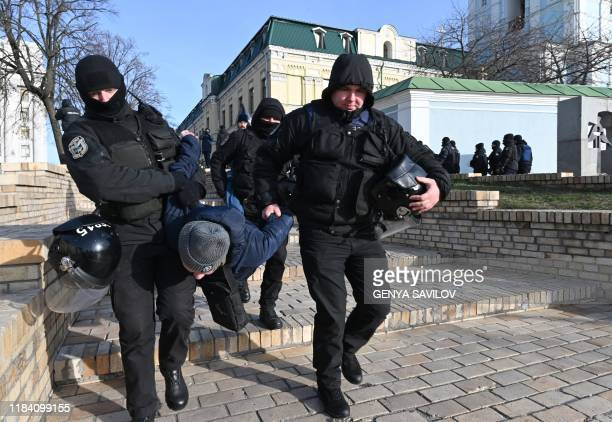 Policemen detain an activist who was protesting against anti-transphobia rally in Kiev on November 23, 2019. - Dozens of people gathered in central...