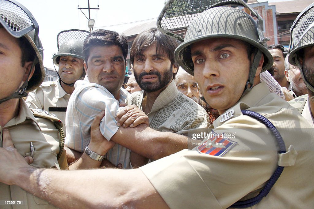 Policemen detain Chairman of Jammu Kashmir Liberation Front Yasin Malik during a protest against killing of 4 people in BSF firing on July 18, 2013 in Srinagar, India. Four people were killed today when security personnel opened fire at a mob that had gathered at a BSF camp in Ramban district protesting against alleged manhandling of an Imam of the area by the force. Curfew would be imposed in Srinagar and all other major towns in the Kashmir Valley from Friday morning as a precautionary measure.